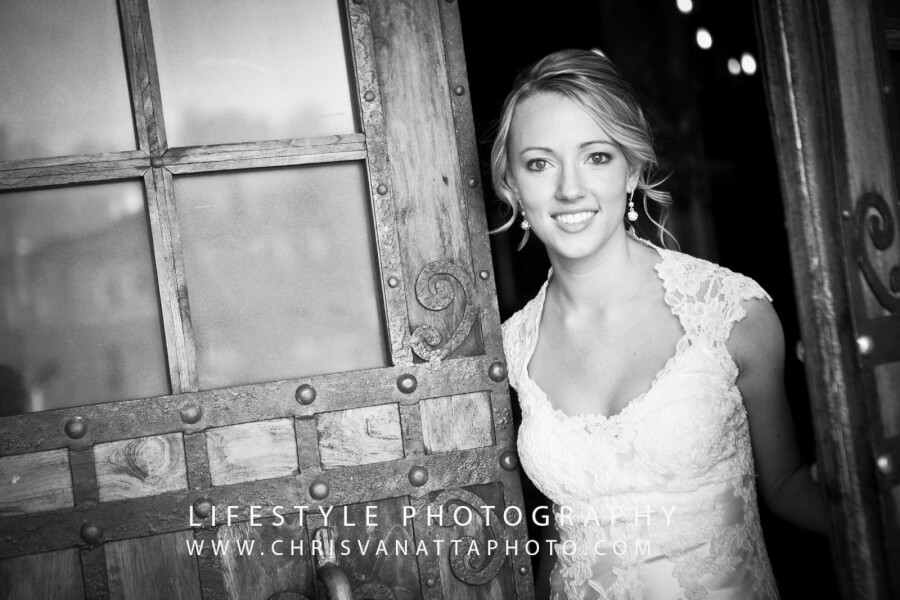Smiling bride in doorway of a church, black & white photo