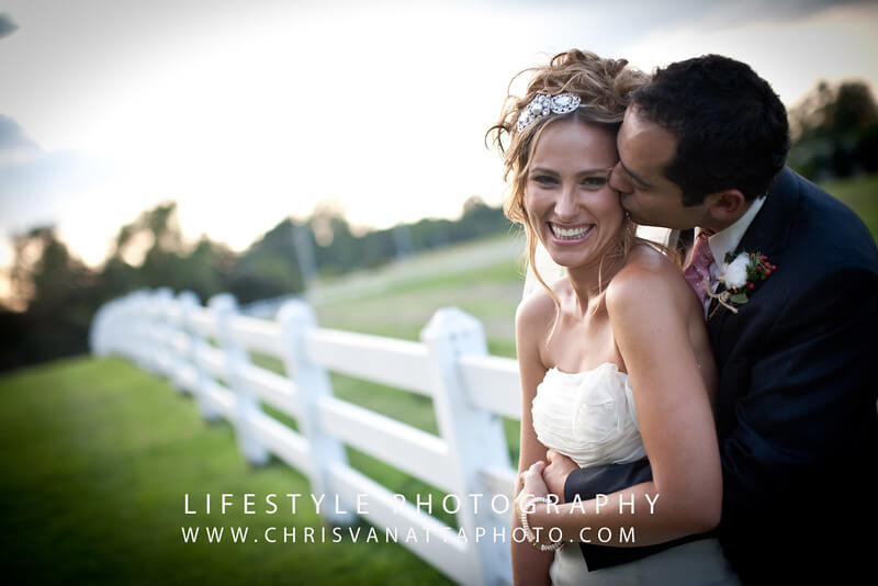 Bride & Groom Kissing against a white fence