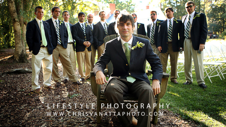 Groom sitting in a chair with groomsmen standing behind him in a row being backlit by the sun.